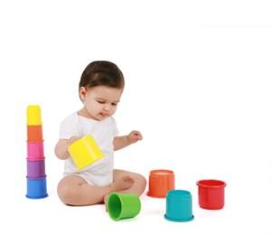 Young baby playing with coloured plastic cups for paediatric physiotherapist to observe